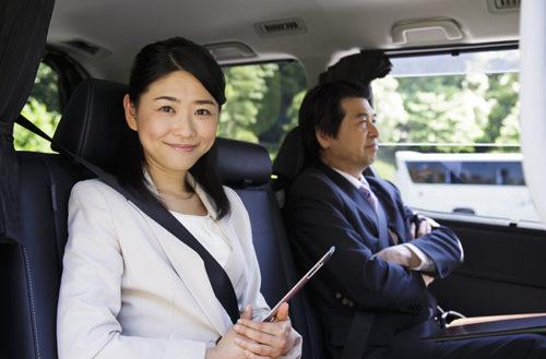 車の前座席に座る女性と男性